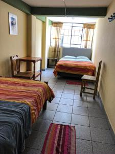 A bed or beds in a room at Hostal Campo Base Huaraz