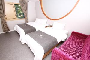 A bed or beds in a room at Amour Hotel