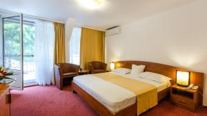 A bed or beds in a room at Hotel Herastrau