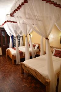 A bed or beds in a room at Masai Lodge