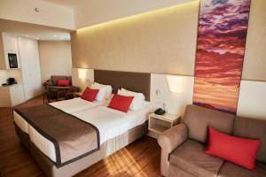 A bed or beds in a room at Ramada Plaza by Wyndham Thraki