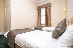 A bed or beds in a room at Borough Arms Hotel