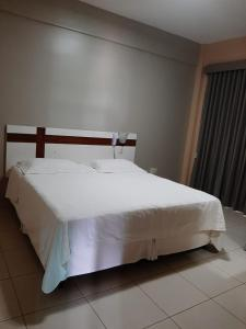 A bed or beds in a room at Amazon Plaza Hotel