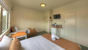 A bed or beds in a room at Hi-Way Motel Grafton