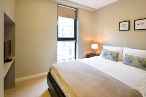 A bed or beds in a room at Victoria One