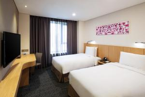 A bed or beds in a room at Tmark Grand Hotel Myeongdong