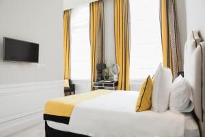 A bed or beds in a room at Clarance Hotel Lille