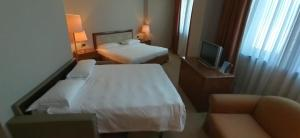 A bed or beds in a room at Tower Genova Airport - Hotel & Conference Center