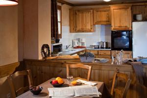A kitchen or kitchenette at CGH Résidences & Spas les Chalets du Soleil Authentiques