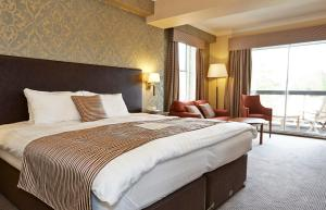 A bed or beds in a room at Bell by Greene King Inns
