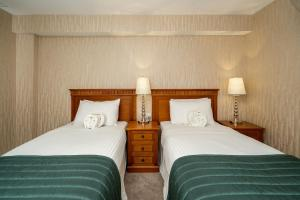 A bed or beds in a room at The Clarendon Hotel