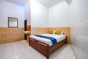 A bed or beds in a room at SPOT ON 2865 Sartika Inn Pati