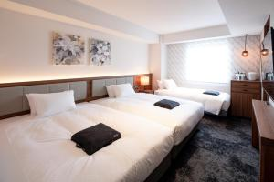 A bed or beds in a room at HOTEL FORZA HAKATAEKI CHIKUSHIGUCHI Ⅱ