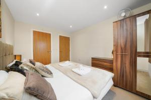 A bed or beds in a room at London Heathrow Living Serviced Apartments by Ferndale