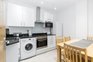 A kitchen or kitchenette at Modern Apartment 2mins walk tube station sleeps 6