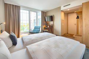 Ein Bett oder Betten in einem Zimmer der Unterkunft LOGINN Hotel Leipzig by ACHAT
