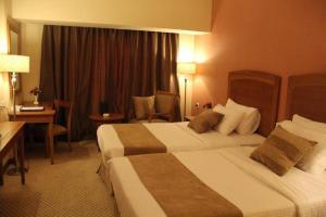 سرير أو أسرّة في غرفة في فندق ريف الملز إنترناشونال