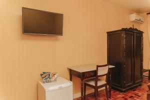 A television and/or entertainment centre at Hotel Pousada Caxiense