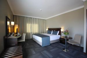A bed or beds in a room at Kaya Prestige