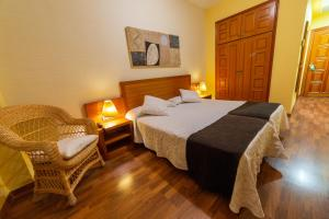 A bed or beds in a room at FONDUQ Hotel Rubielos