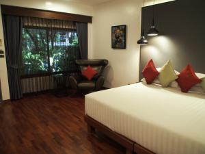 A bed or beds in a room at Laluna Hotel And Resort, Chiang Rai