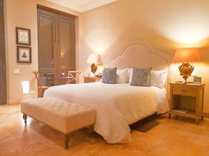 A bed or beds in a room at Bastión Luxury Hotel