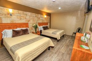 A bed or beds in a room at Hotel Mansion del Cantador