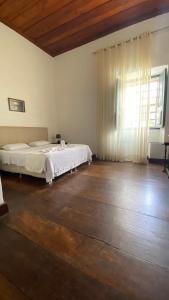 A bed or beds in a room at Pousada Convento do Carmo