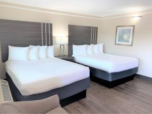 A bed or beds in a room at Summerfield Inn Fresno Yosemite