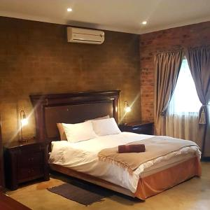 A bed or beds in a room at Maretlwane Guesthouse