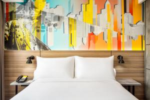 A bed or beds in a room at ibis Styles Bekasi Jatibening