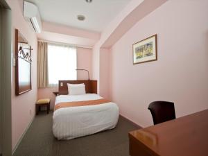 A bed or beds in a room at Hotel Palm Royal Naha Kokusai Street