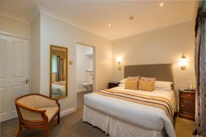 A bed or beds in a room at Glen-Yr-Afon House Hotel