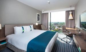 A bed or beds in a room at Holiday Inn London West
