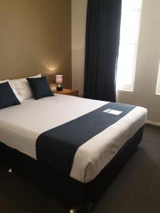 A bed or beds in a room at Adelaide Pulteney Motel
