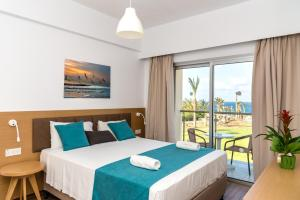 A bed or beds in a room at Helios Bay Hotel and Suites