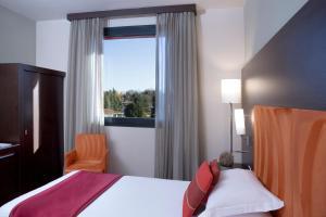 A bed or beds in a room at Hilton Garden Inn Milan Malpensa