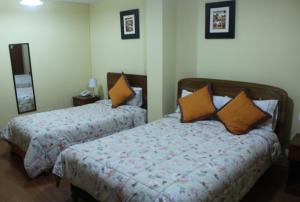 A bed or beds in a room at Yuraq Hotel