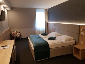 A bed or beds in a room at Hotel Alpina