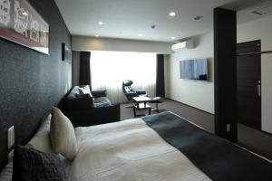 A bed or beds in a room at Randor Residential Hotel Sapporo Suites