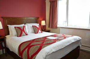 A bed or beds in a room at Commodore Hotel by Greene King Inns