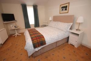 A bed or beds in a room at Inglestone House Guest House