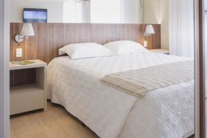 A bed or beds in a room at Aquarius Hotel Flat Residence