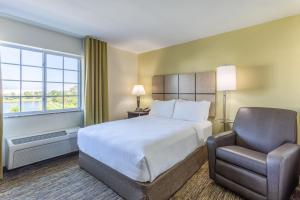 A bed or beds in a room at Candlewood Suites Aurora-Naperville