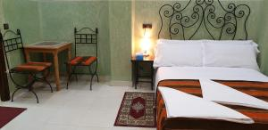 A bed or beds in a room at HOTEL AFRIQUIA GARDEN