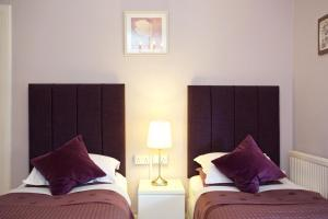 A bed or beds in a room at Pitcullen Guest House