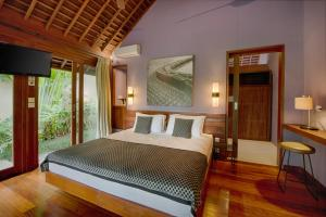 A bed or beds in a room at Temuku Villas Ubud