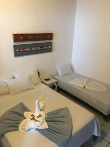A bed or beds in a room at Pousada do Carlos