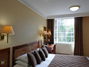 A bed or beds in a room at Grange Clarendon Hotel