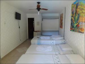 A bed or beds in a room at Hotel Tubarão